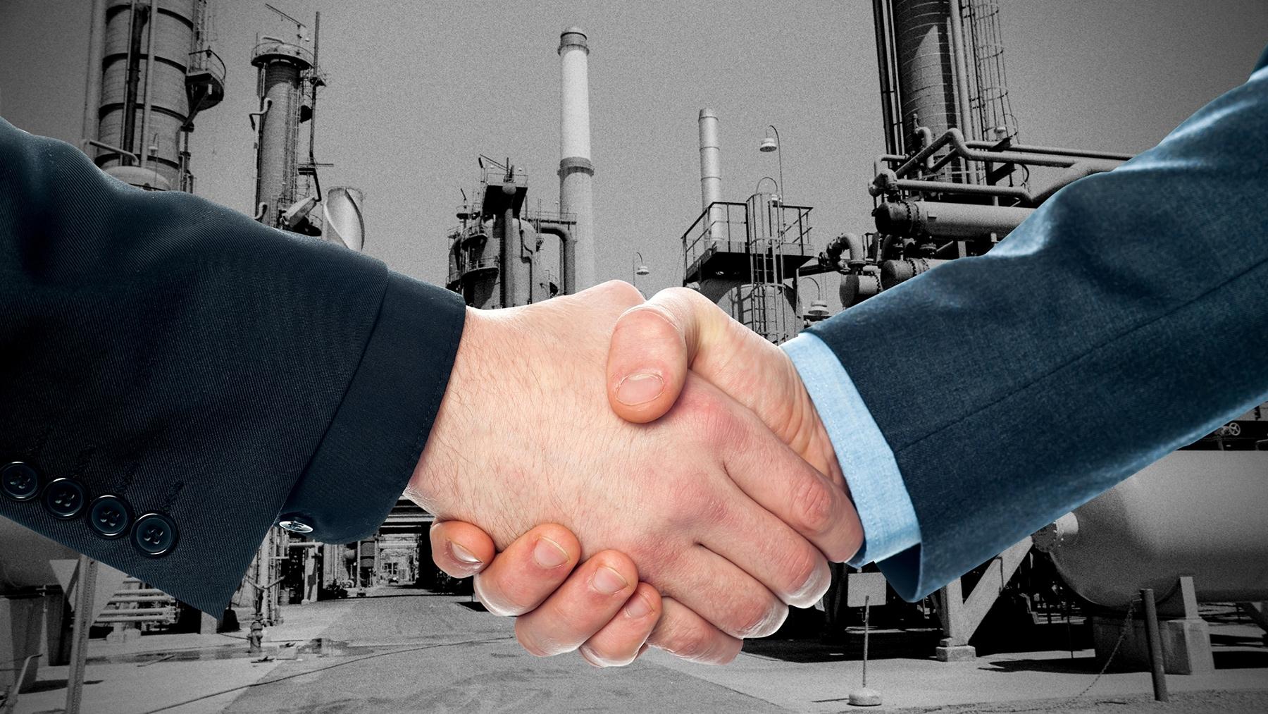 Handshake over image of oil refinery